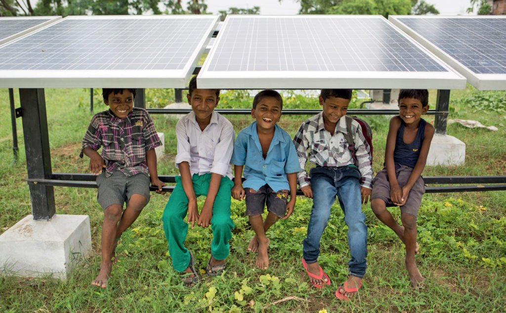 Five smiling underprivileged children sitting under a solar panel